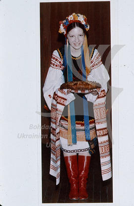 A girl in Ukrainian national costume holding korovai (welcoming bread) on an embroidered rushnyk ...