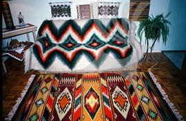 A living room decorated with embroidered pillows and woven carpets